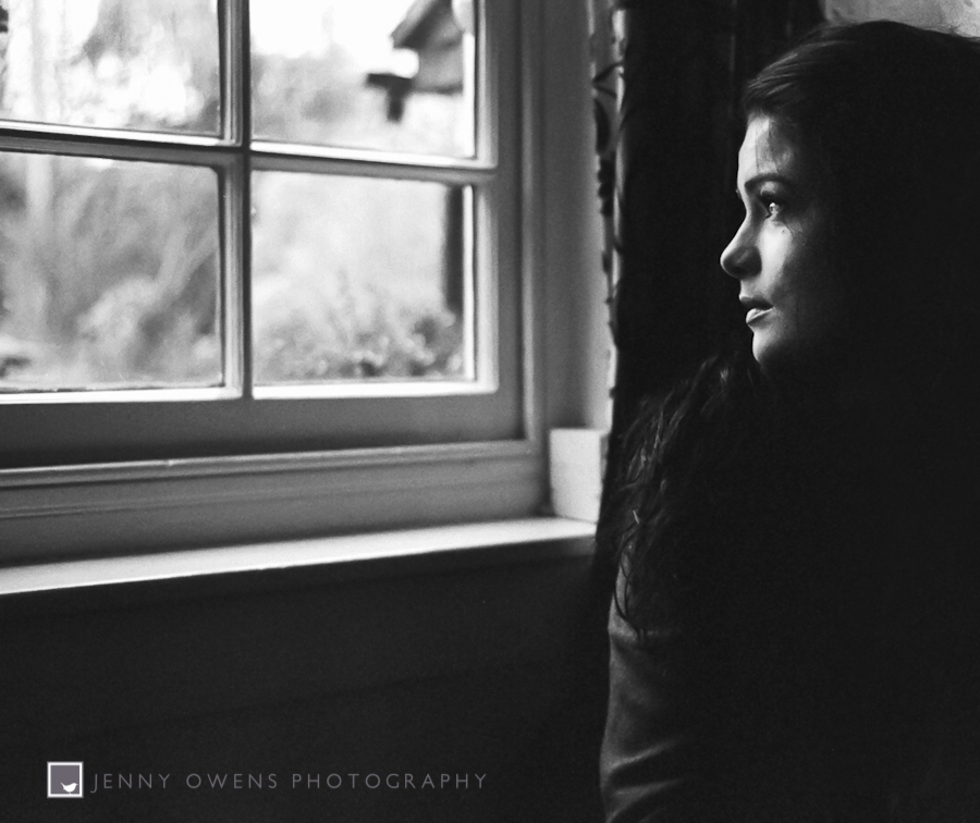 portrait of a girl by window black and white professional photography