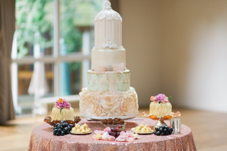 cake table with grapes, miringues andtiered wedding cake with birdcage above and smaller cakes on the side