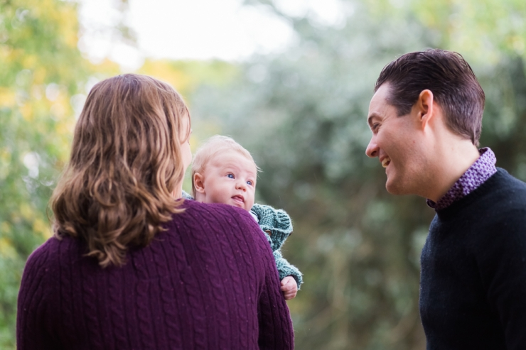 baby with Mum looking at Dad in New Forest session with Jenny Owens Photography