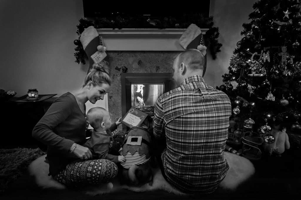 black and white family christmas scene infront of fireplace
