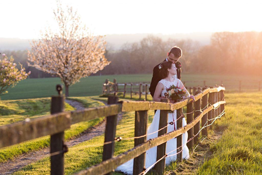 bride and groom by fence at teh golden hour Bonhams barn