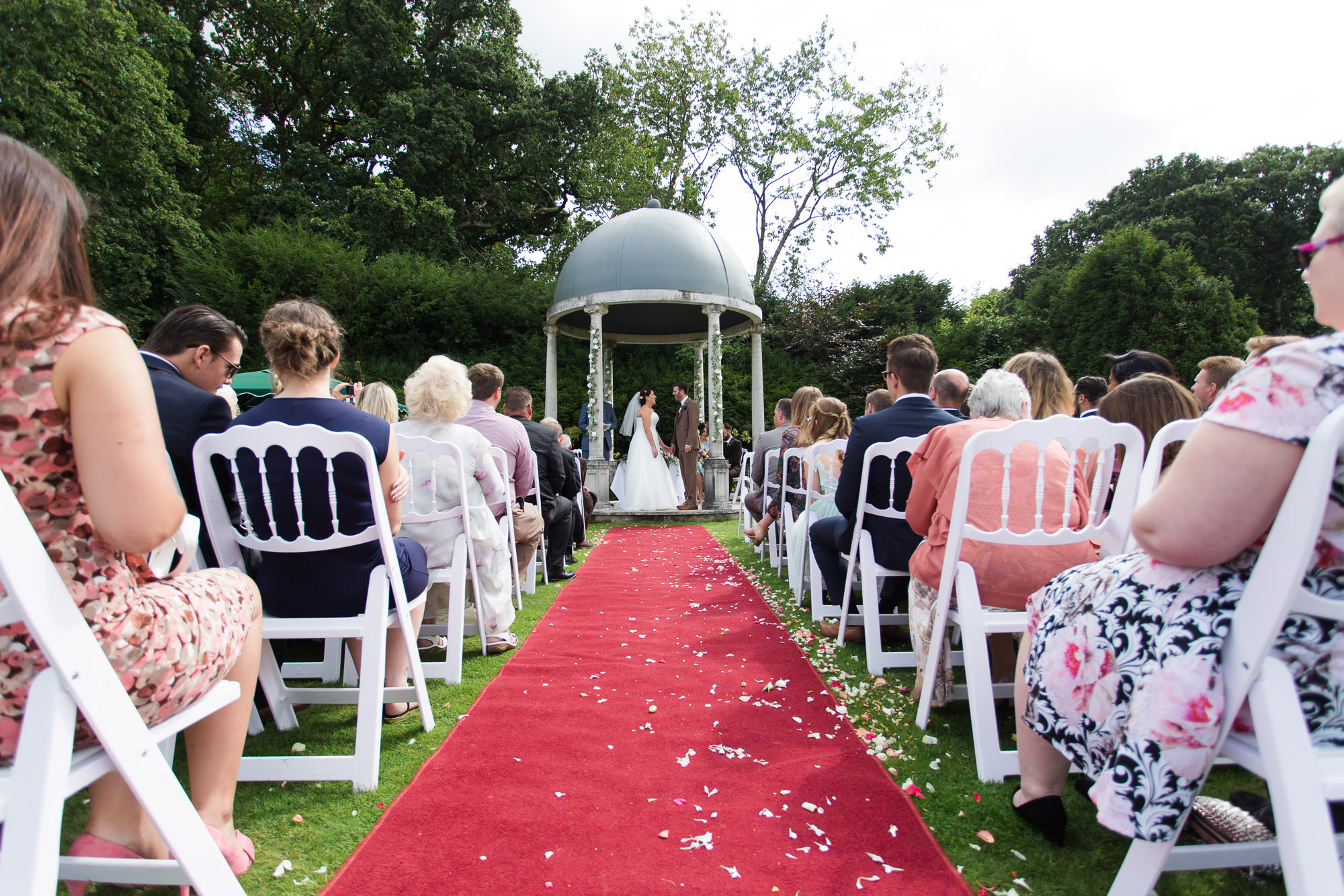 Outdoor wedding ceremony view from aisle at Rhinefield House Hotel by Jenny Owens Photography
