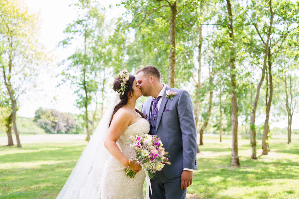 Bride and groom kissing infront of trees at Skylar Golf and Country Club by Jenny Owens Photography