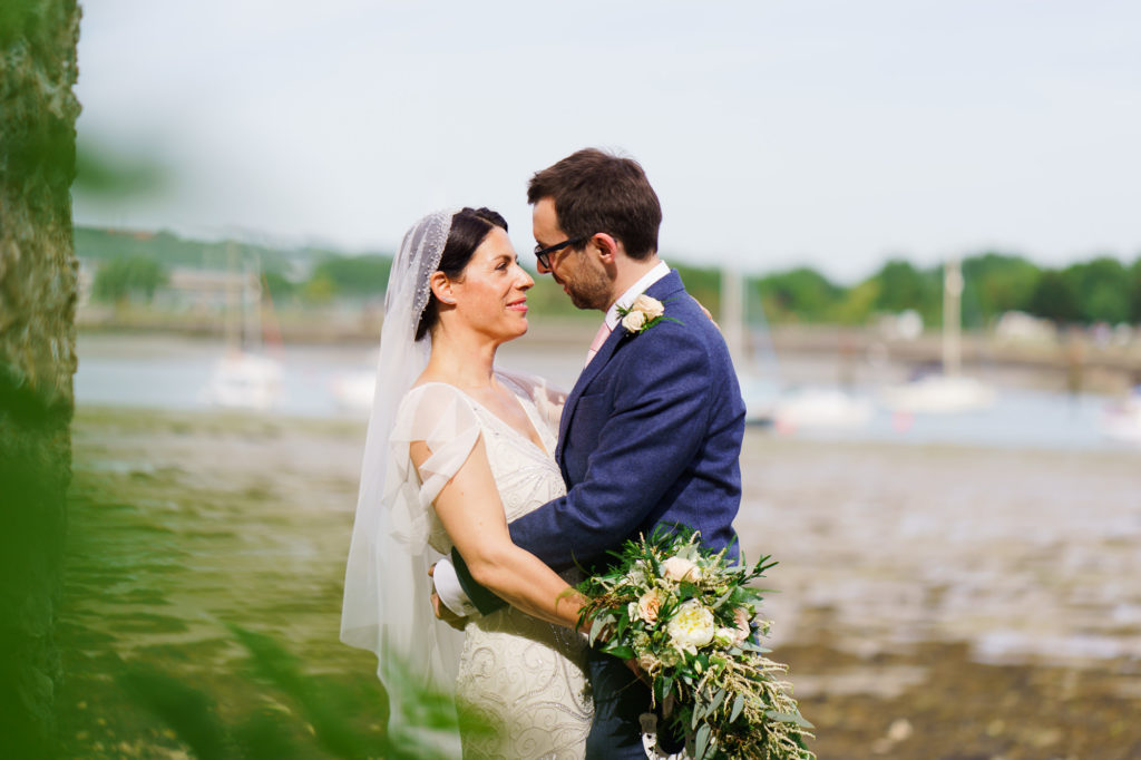 bride and groom looking at each other in an emabrace outside Portchester castle wedding