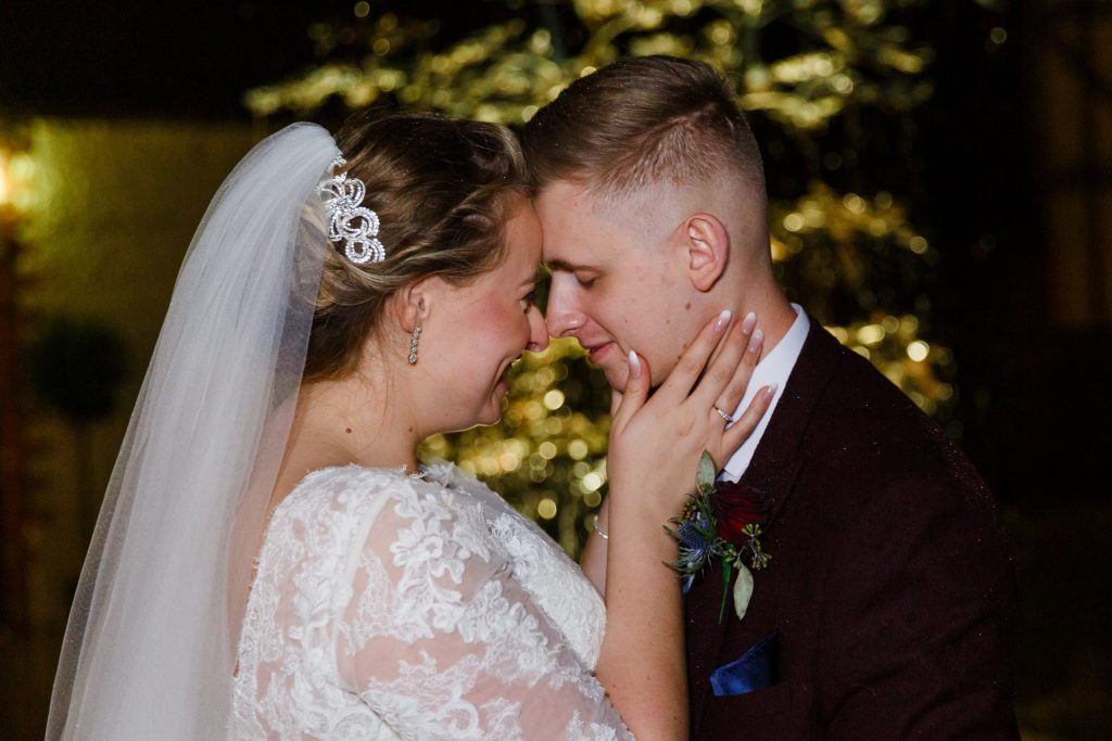 brdie and groom infront of twinkling lights of the fountain at rivervale barn by jenny owens photography