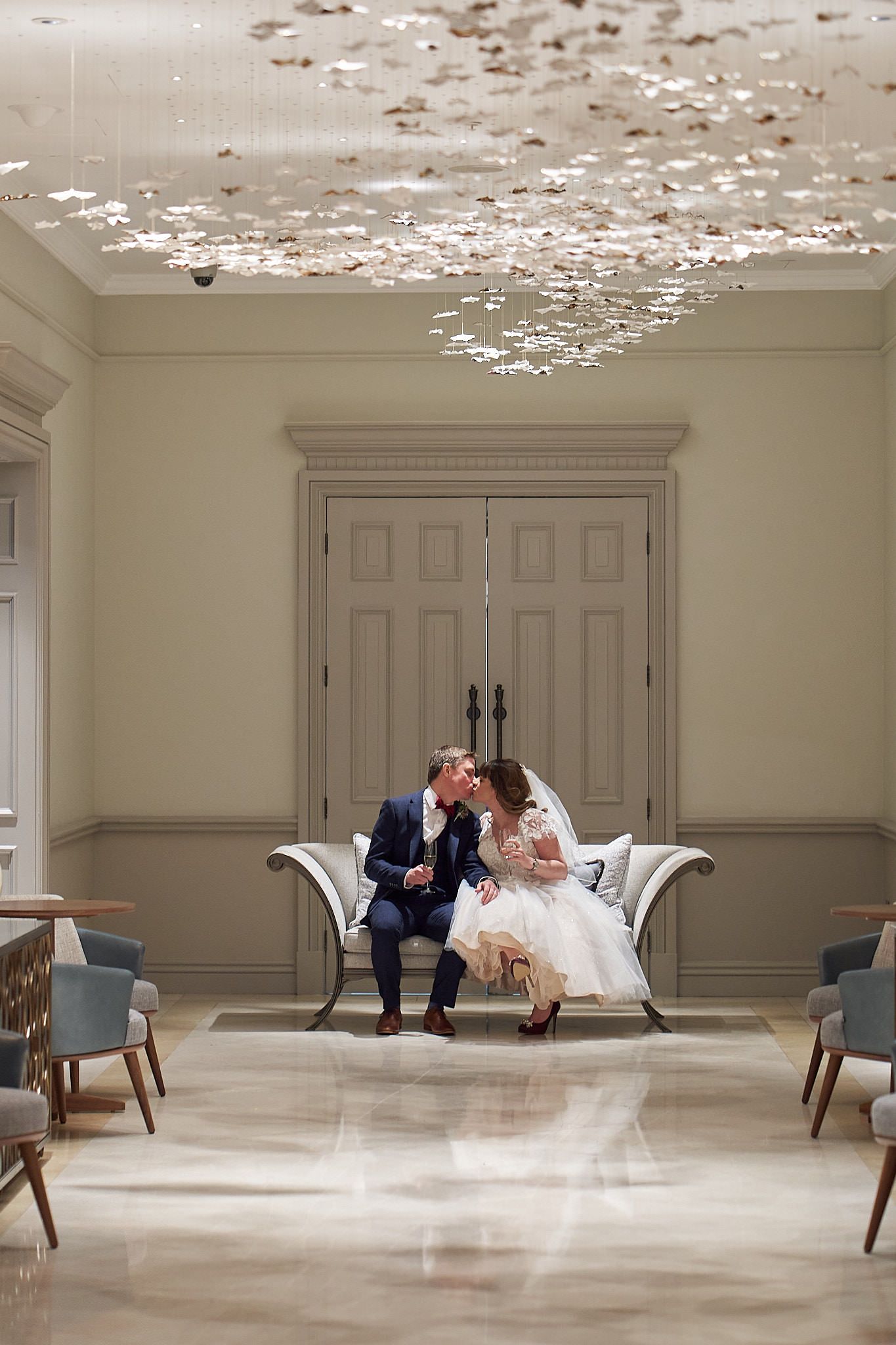 brdie and groom sitting on a sofa at the end of a corridor at four seasons hotel hampshire