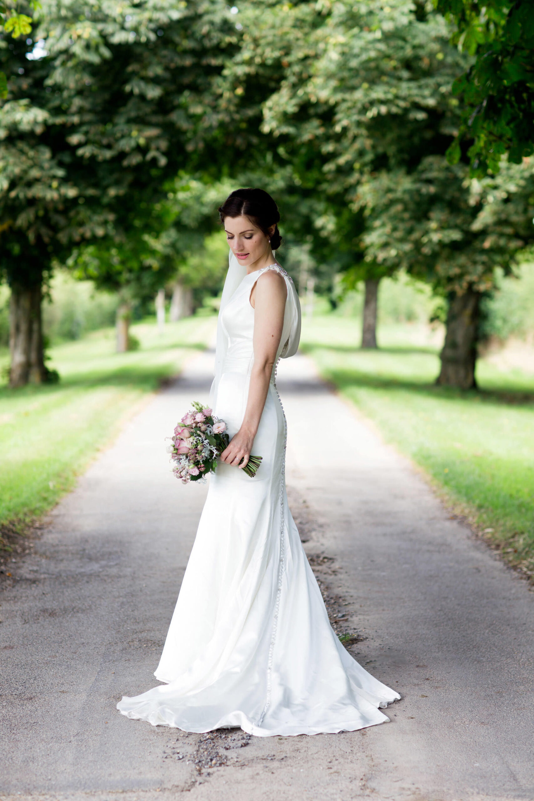 bride standing on her own in green driveway