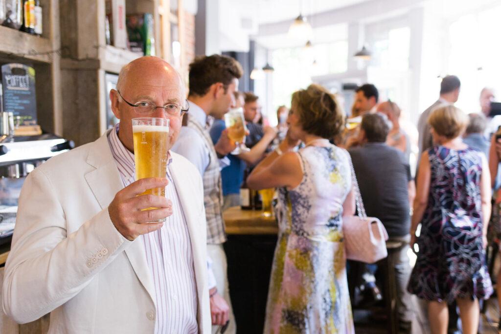 man raising a pint documentary wedding photography