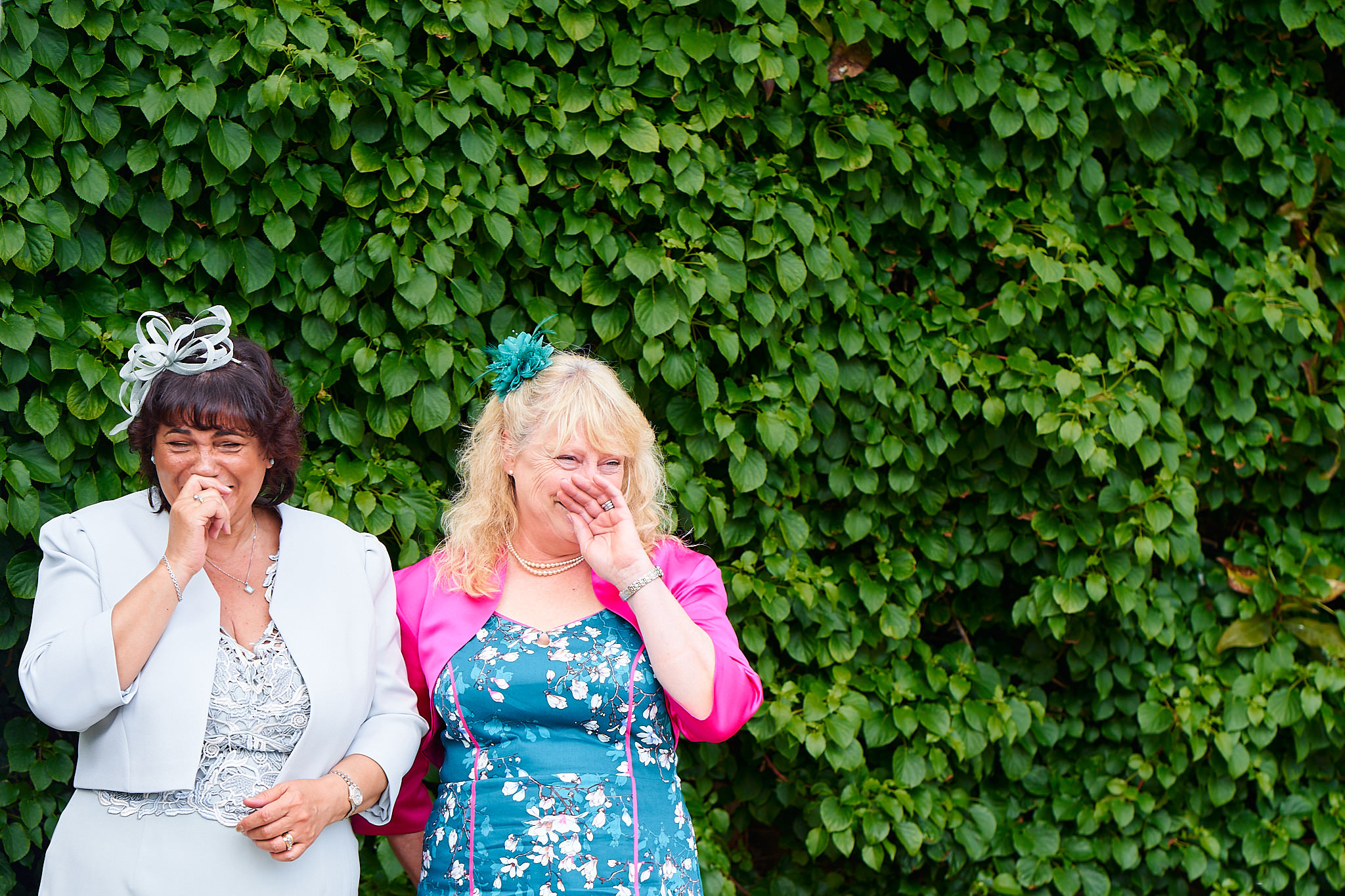 mother of bride and mother of groom giggling outside avington park