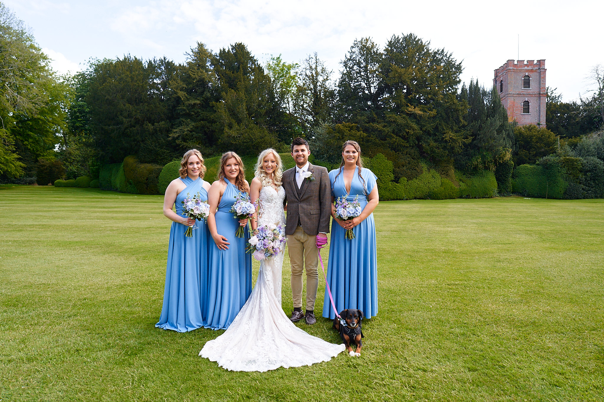 bride and groom and bridesmaids in blue and pet puppy