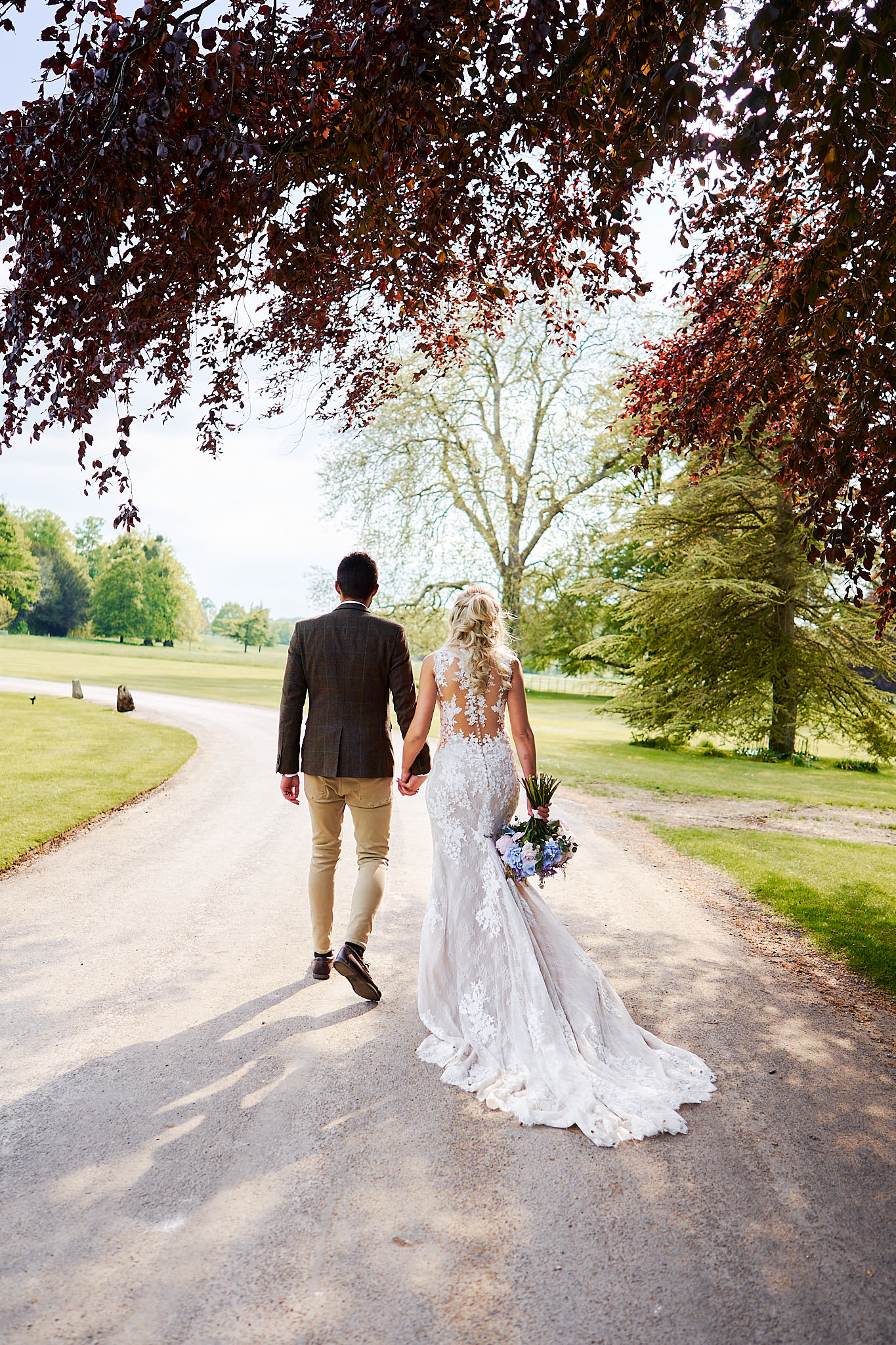 bride and groom walking outside avington park
