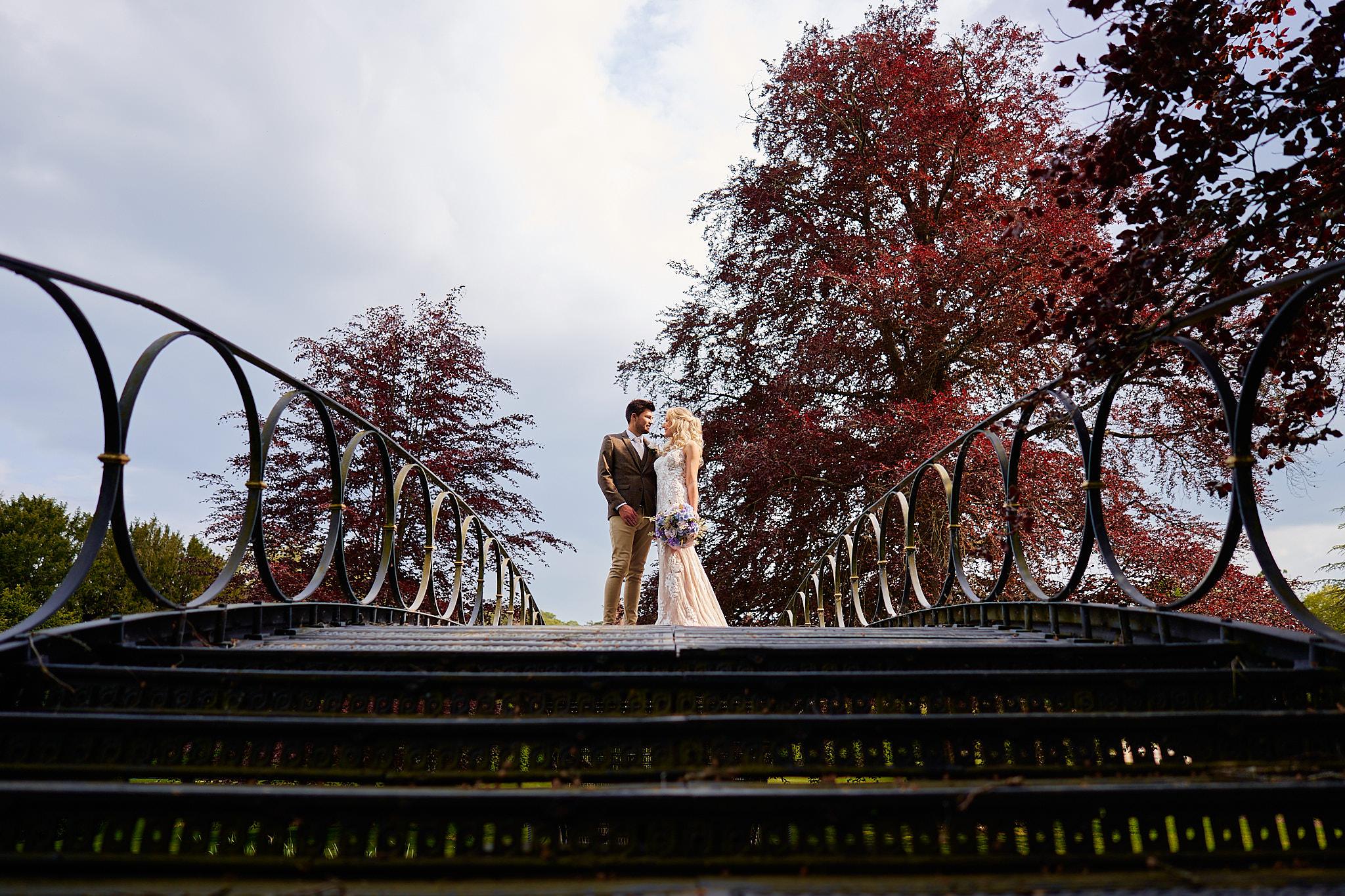 bride and groom on bridge at avington park manor house