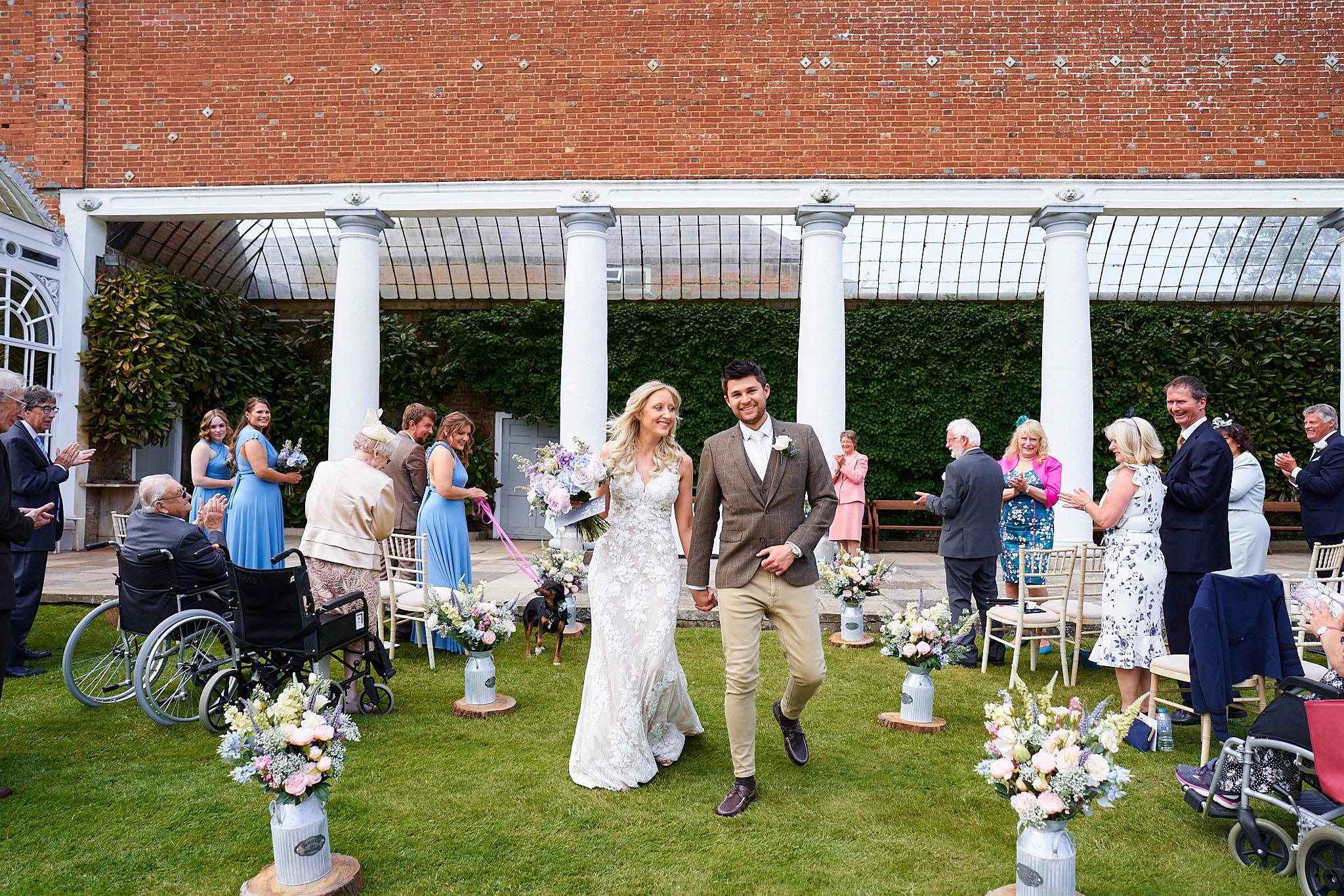 brdie and groom walking down the aisle outside avington park manor house