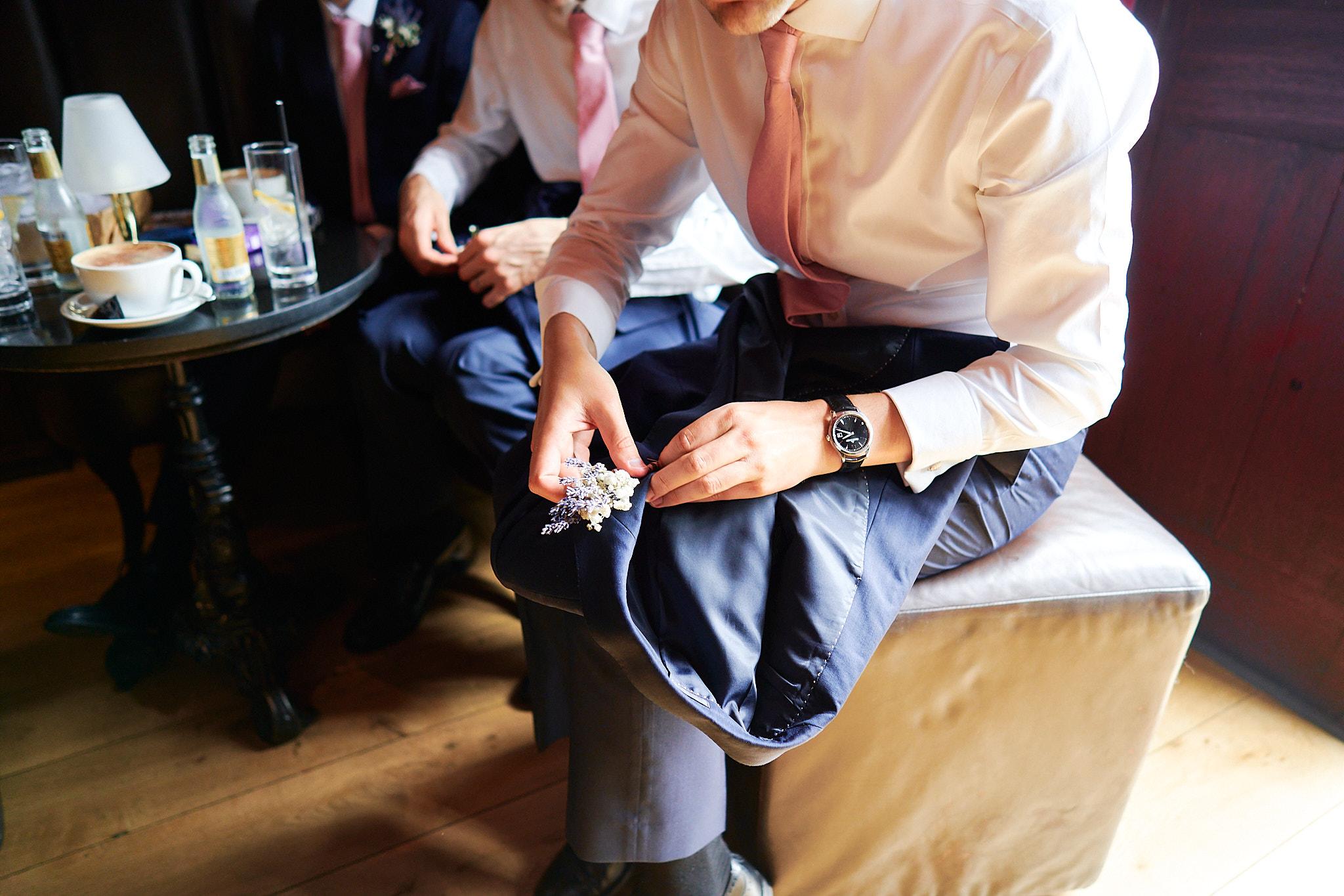 best men pinning the buttonholes