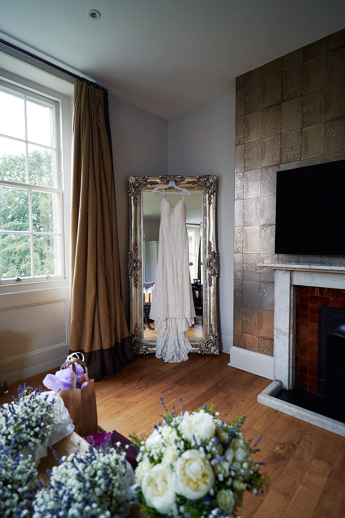 wedding dress hanging on ornate mirror jenny owens photography