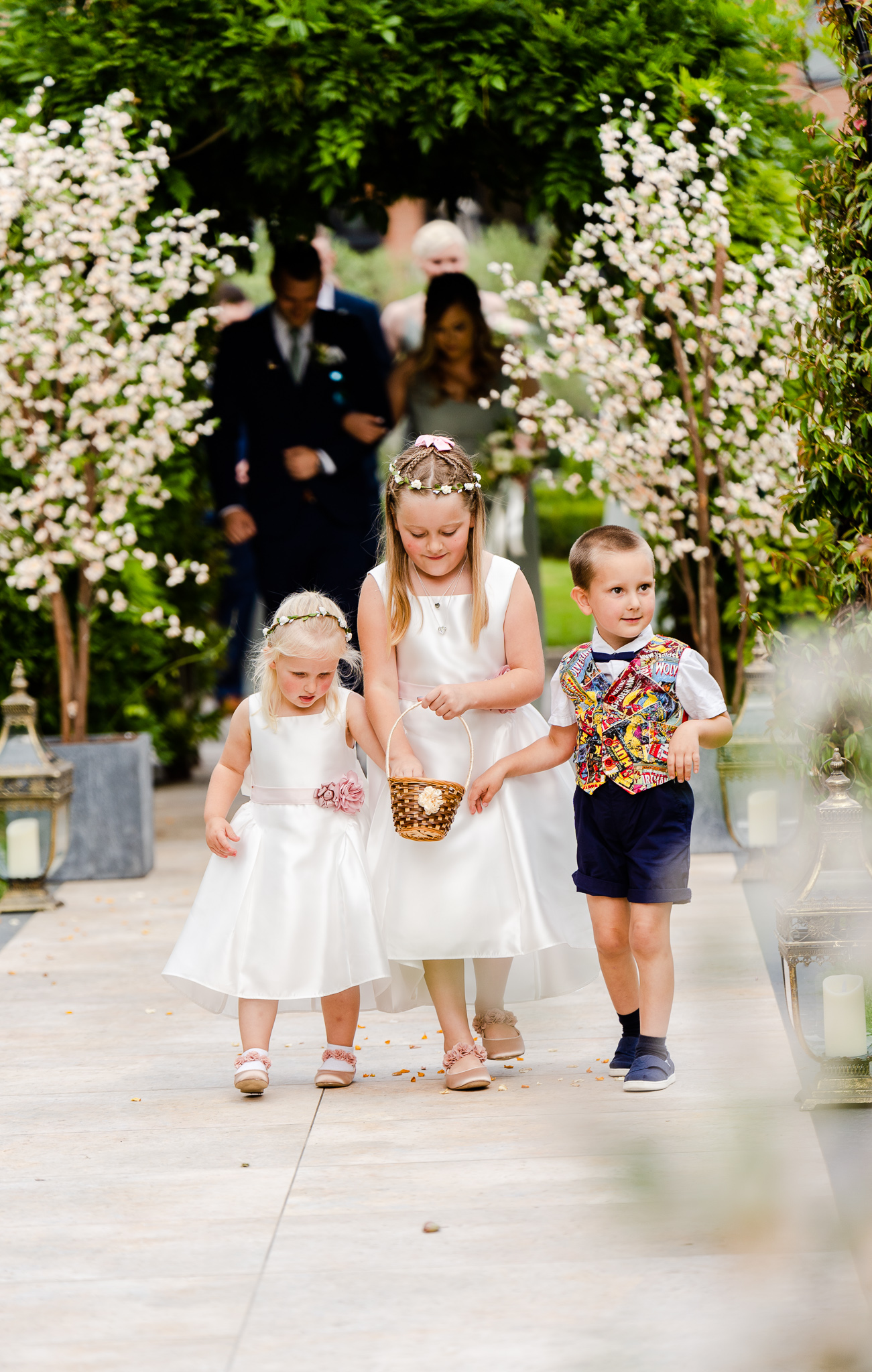 flowers girls and pageboys walking down the outdoor ceremony aisle