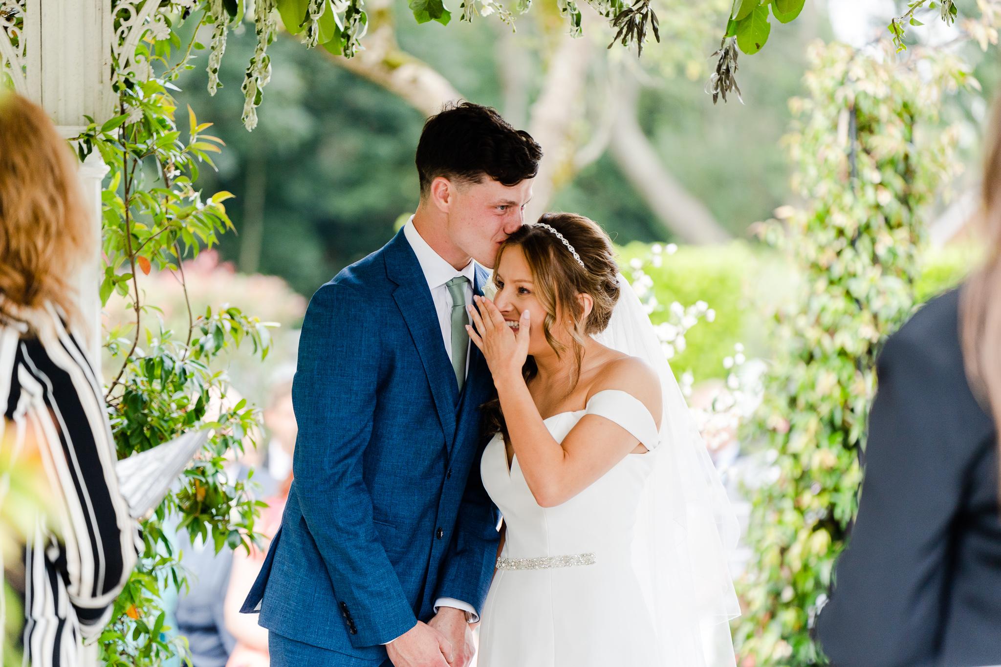 groom kissing brdie on head outside before their ceremony