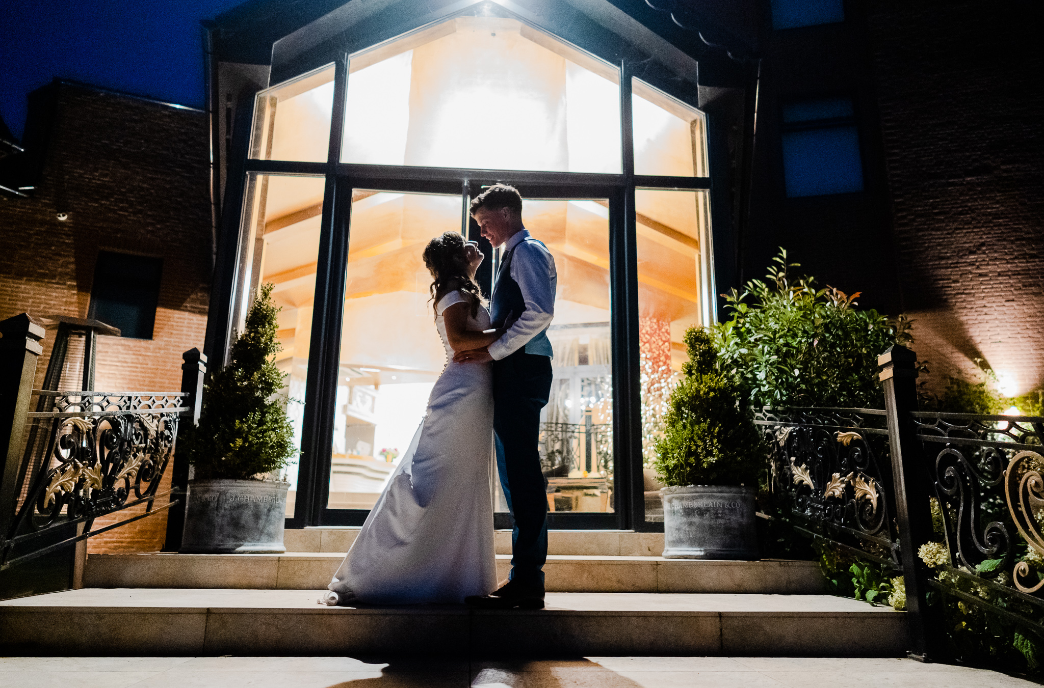 almost silhouette shot of brdie and groom at night in front of guildford manor hotel