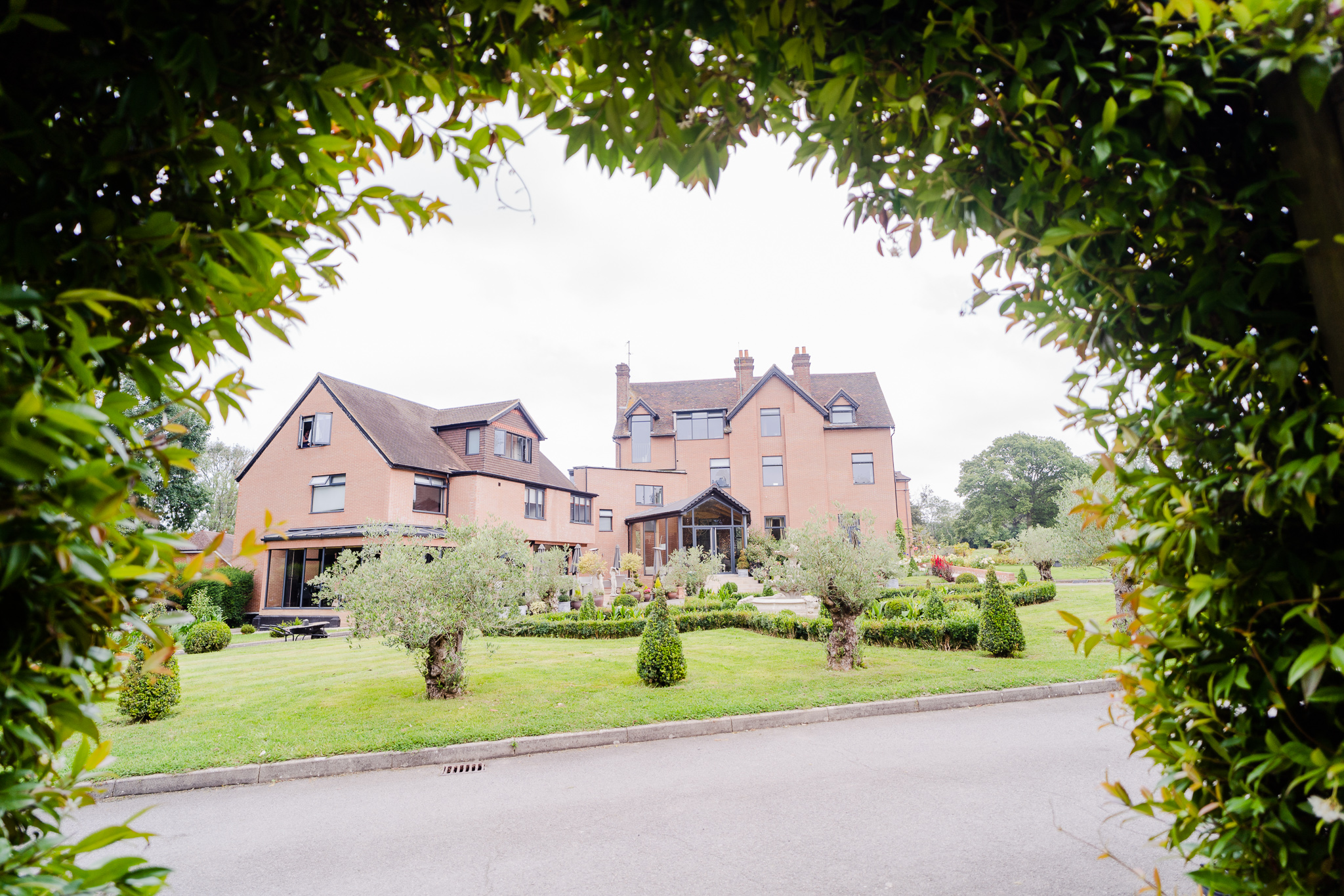 guildford manor hotel framed by arch from their outdoor ceremony space