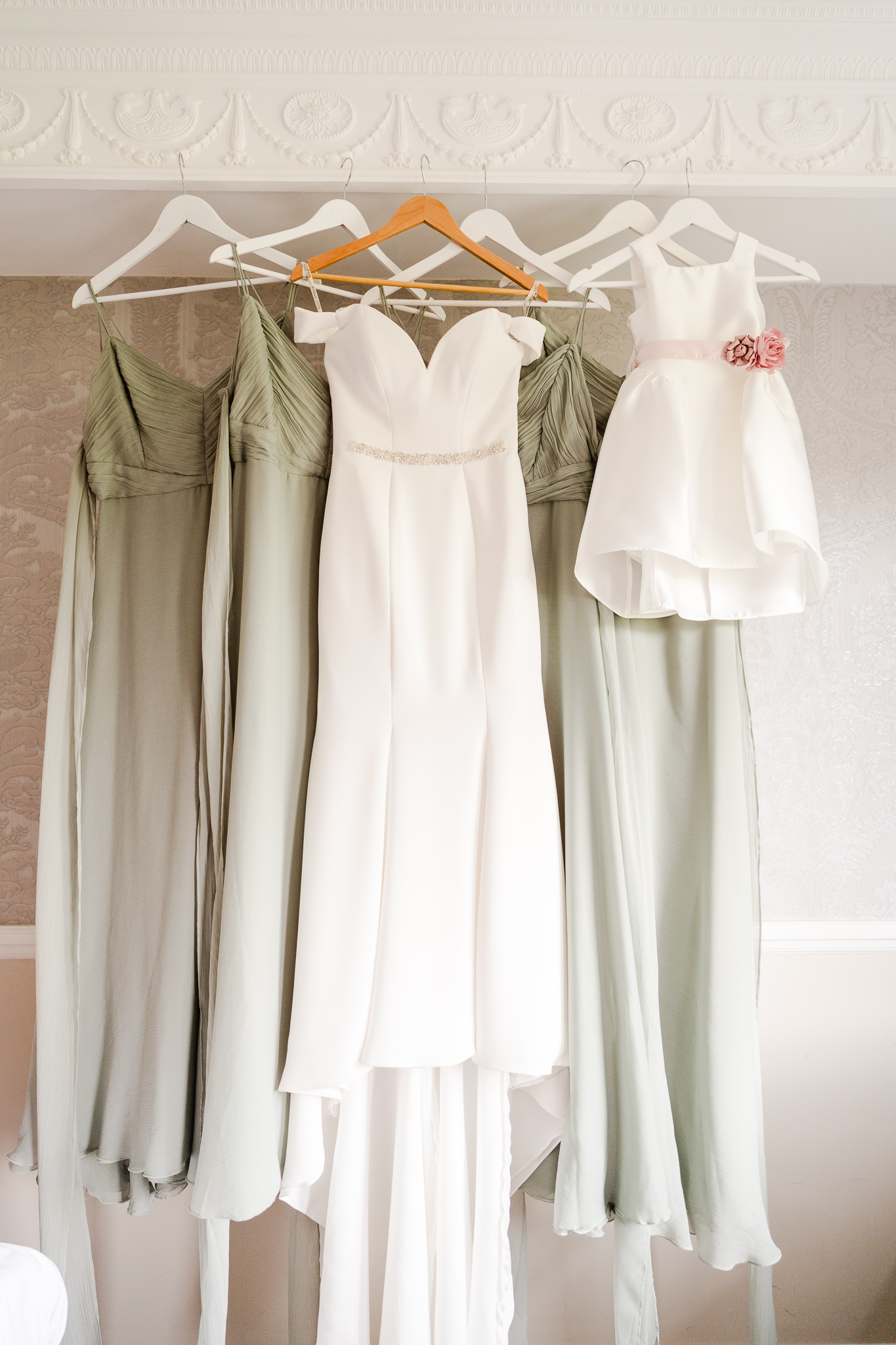 picture of brdie's wedding gown, green brdiesmaid dresses and flower girl dress hanging up