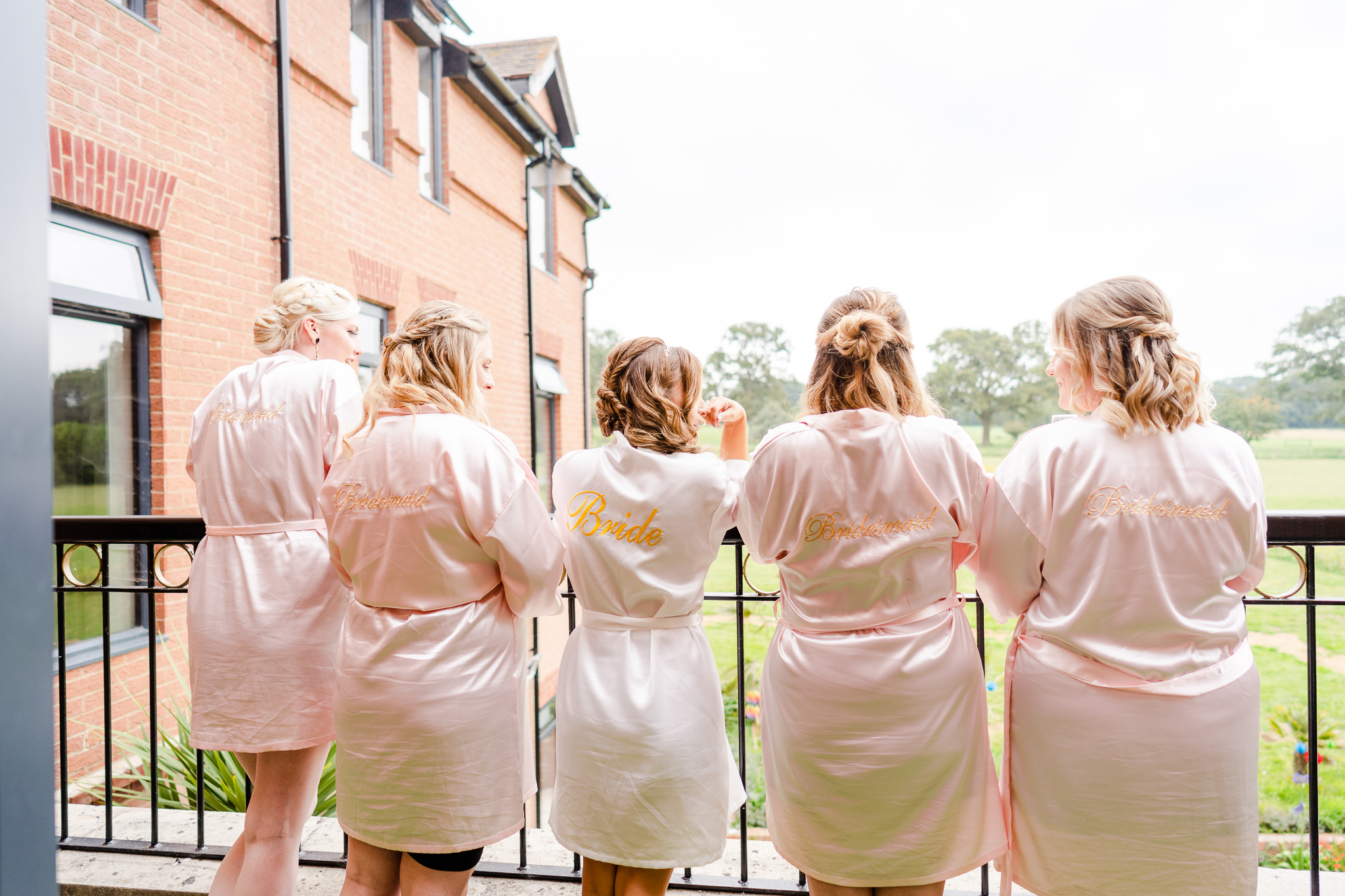 bride and her bridesmaids looking out of balcony