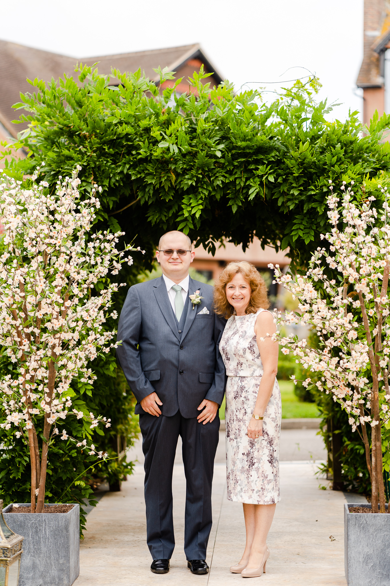 mother of bride and brother walking down outdoor ceremony space in september wedding