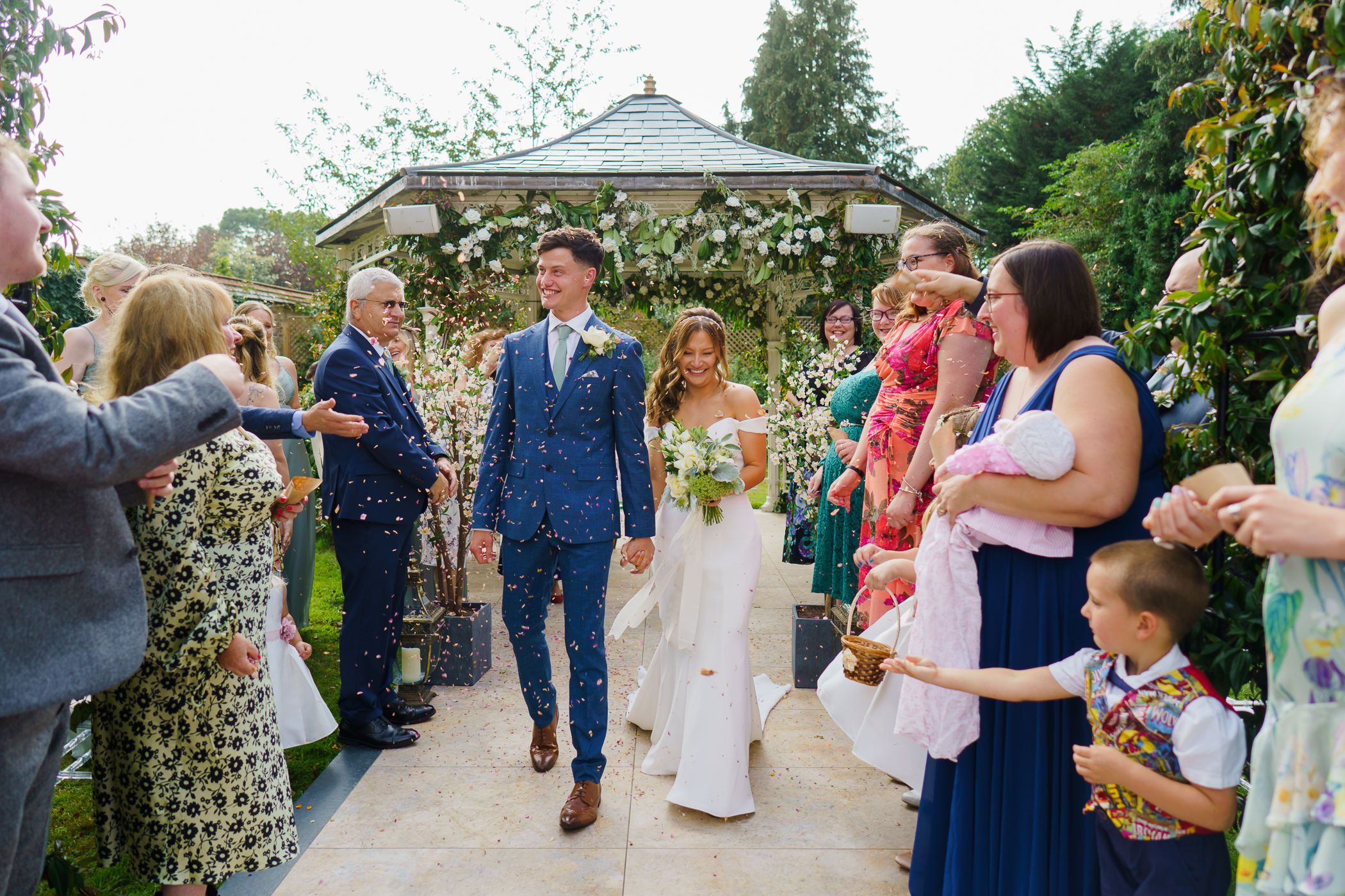 brdie and groom walking down the outdoor ceremony aisle with guests trhowing confetti