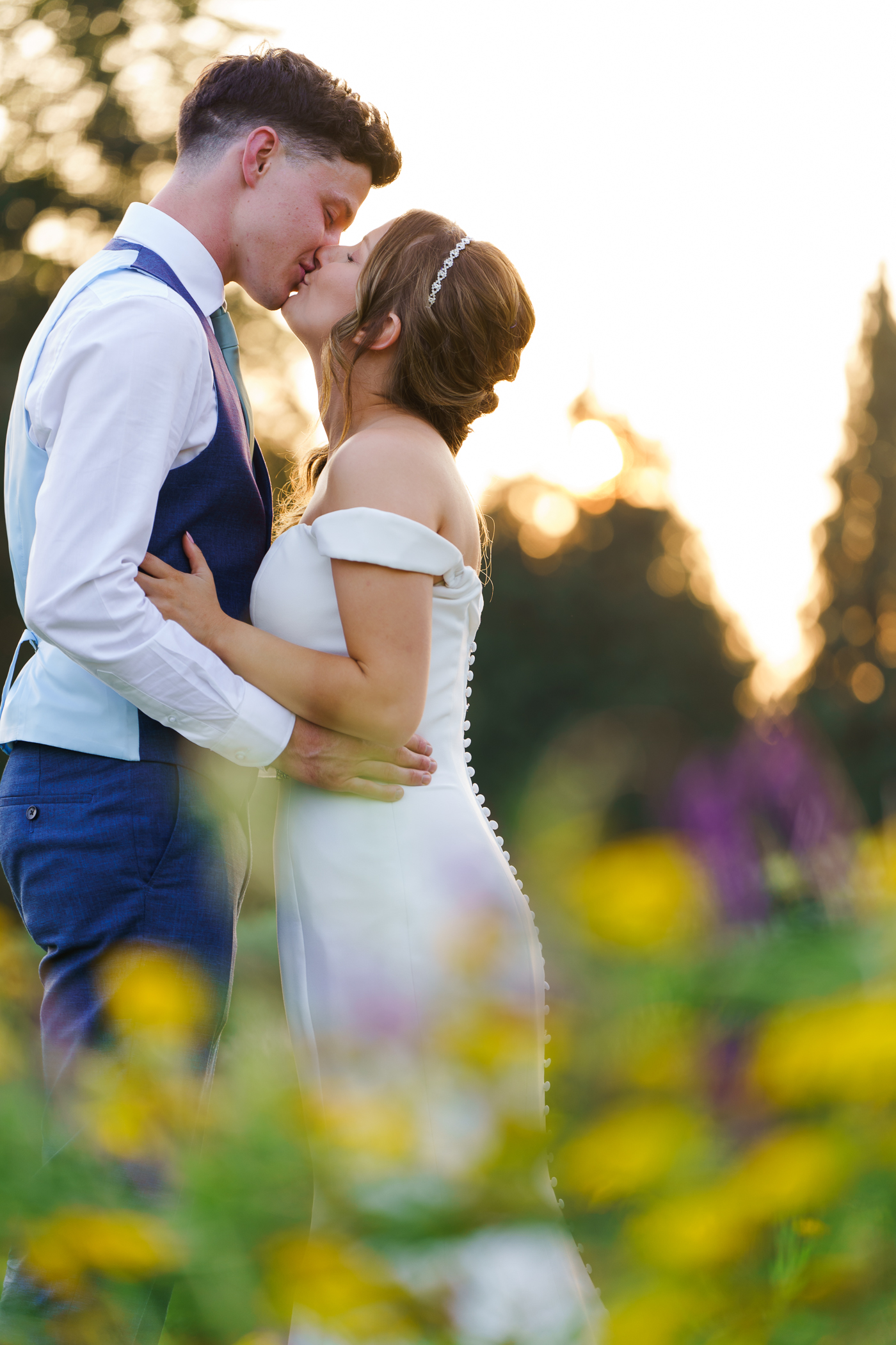 beautiful golden hour photo of brdie and groom kissing in field surrounded by wild flowers