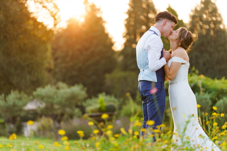 romantic golden hour photo and bride and groom in wildflower meadow field