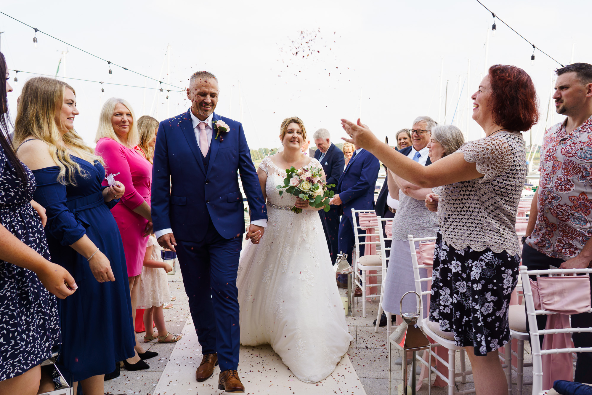 bride and groom walking down to confetti throw at royal southern yacht club outdoor ceremony