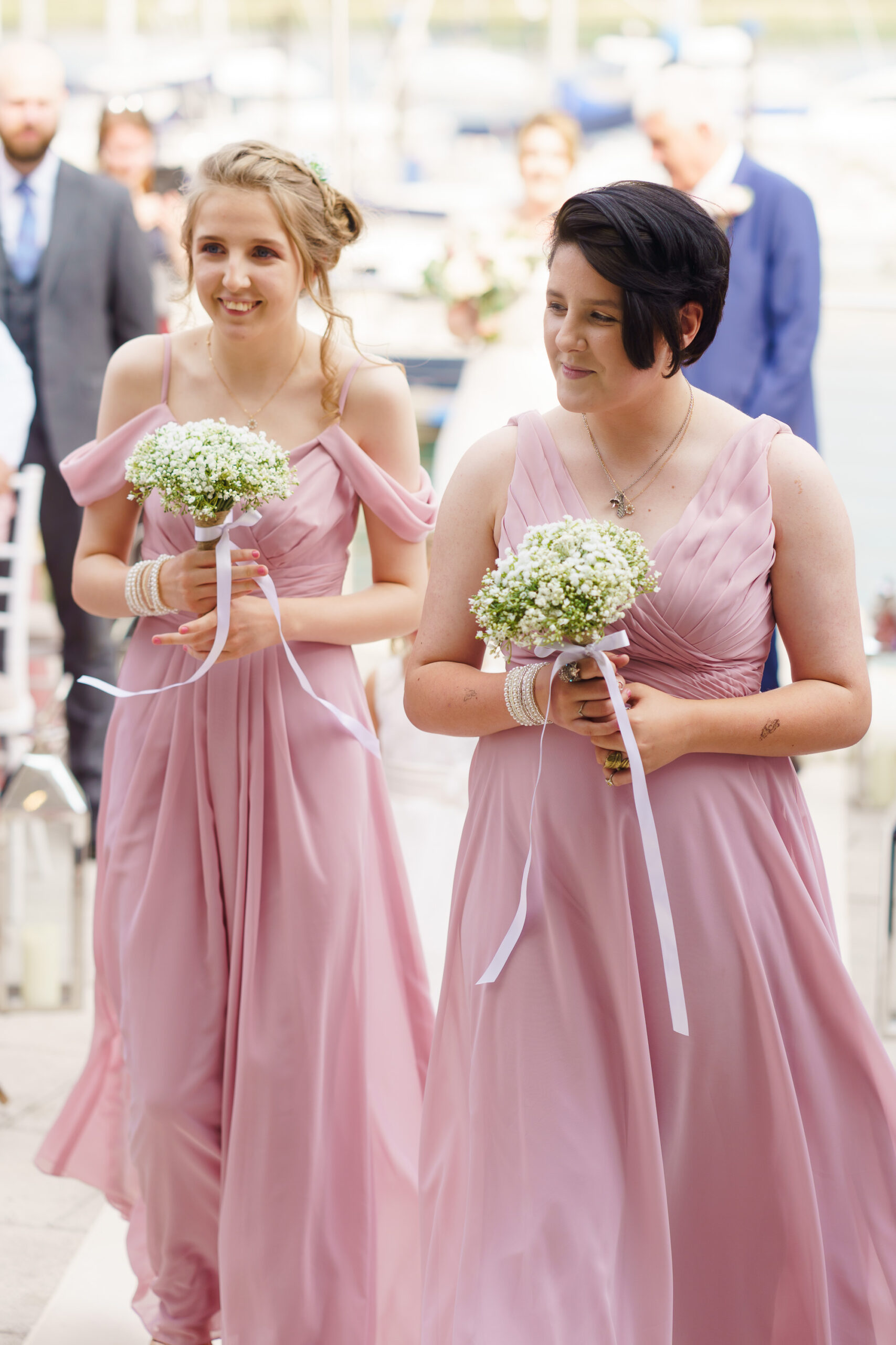 bridesmaids in pink walking up the aisle at outdoor wedding by the hamble river