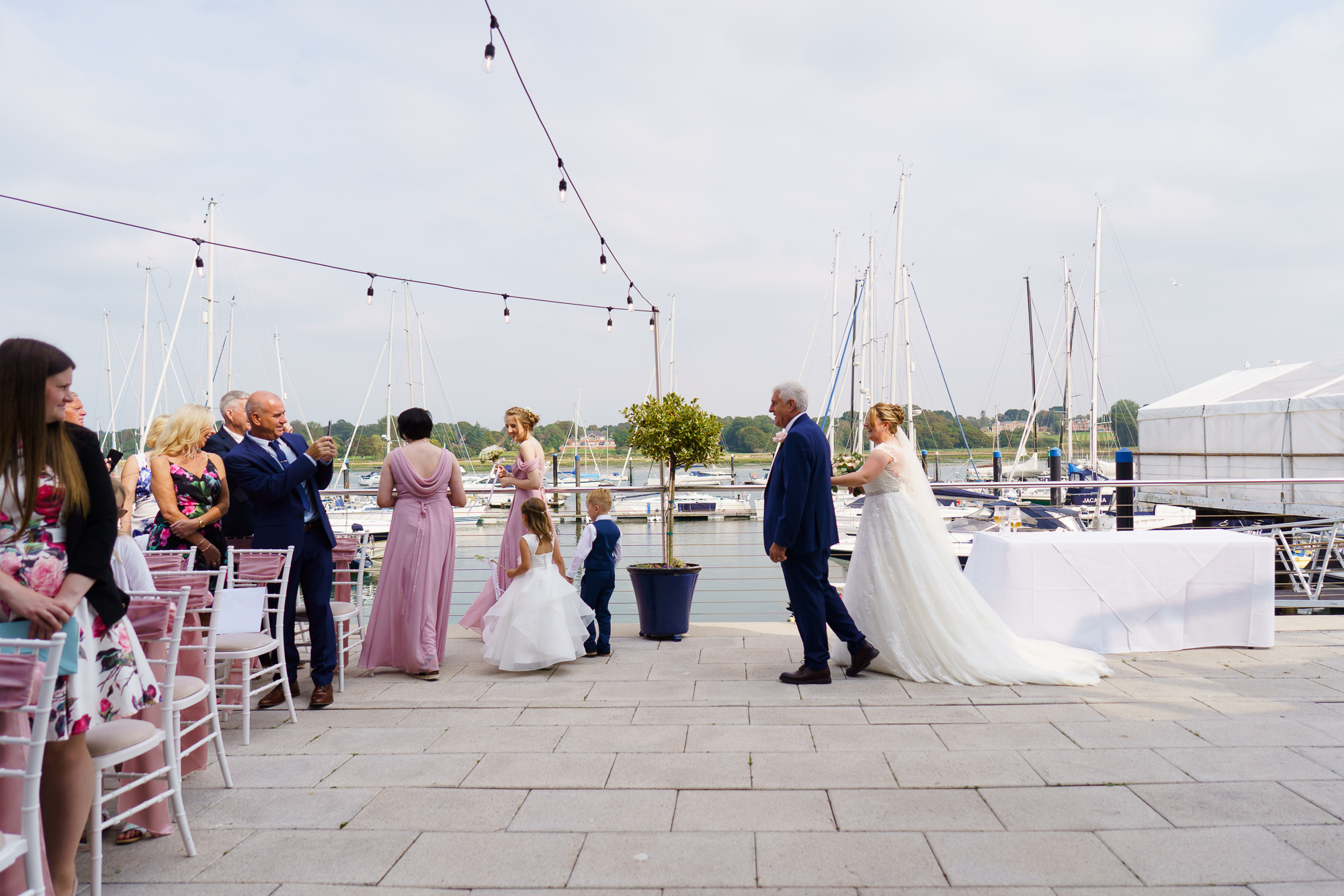 bridal party walking up the aisle at outdoor wedding at roayl southern yacht club