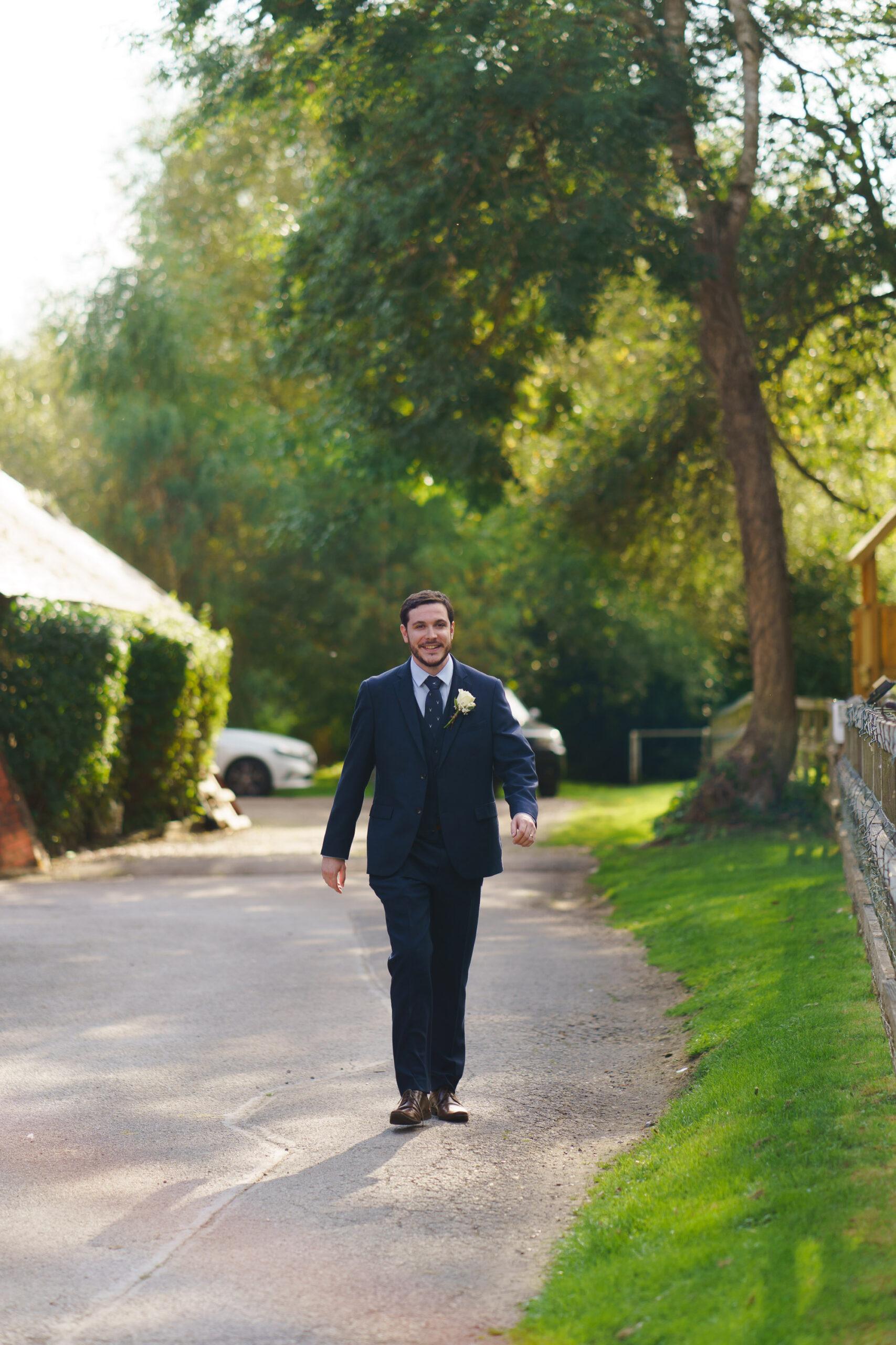 photo of groom walking down lane at Bourne Valley Inn