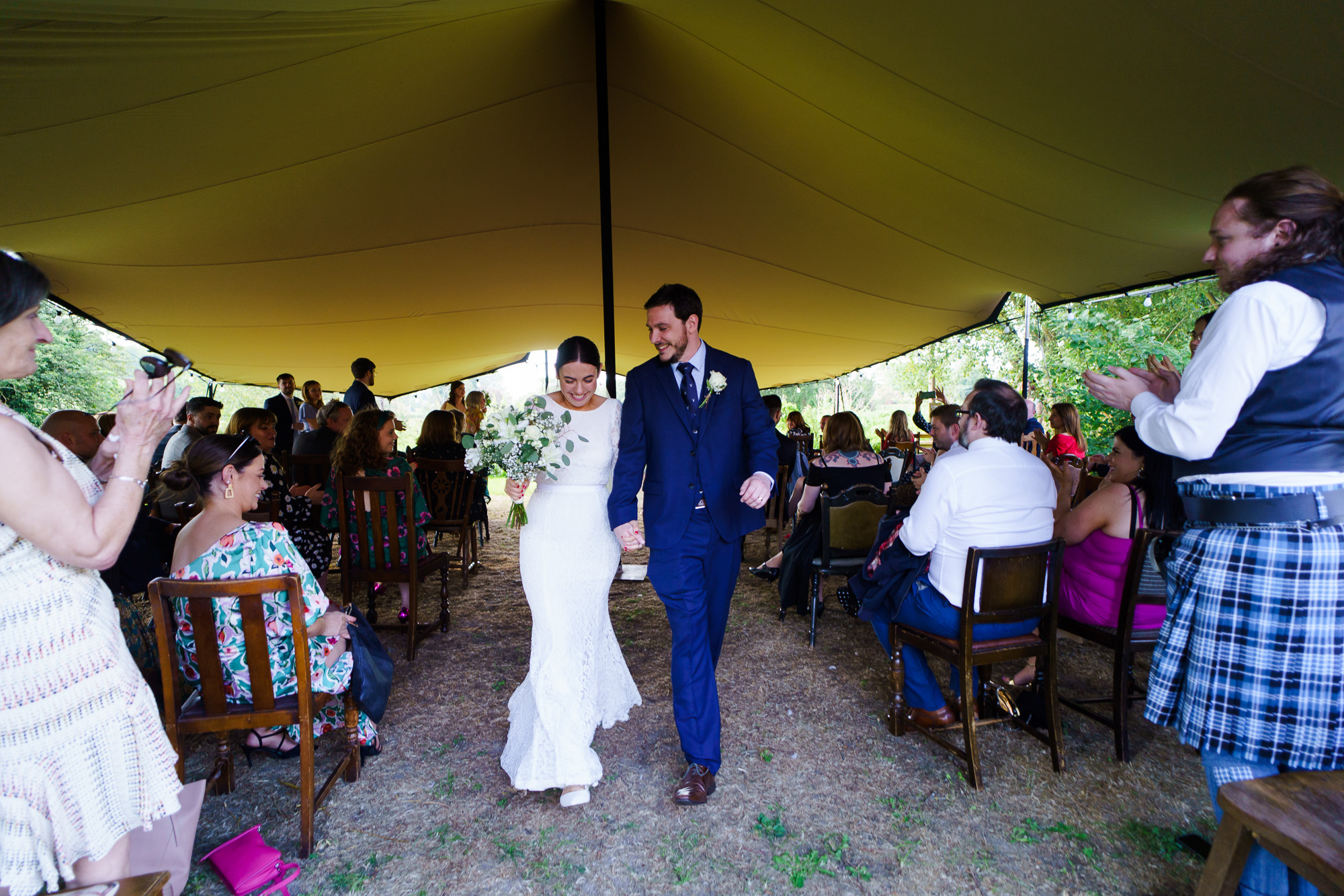 brdie and groom exit their vow renewal under tipi at Bourne Valley Inn
