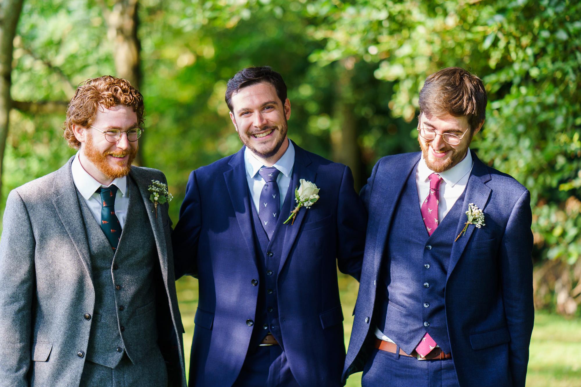 Informal portrait of groom and groomsmen laughing in gardens of Bourne Valley Inn