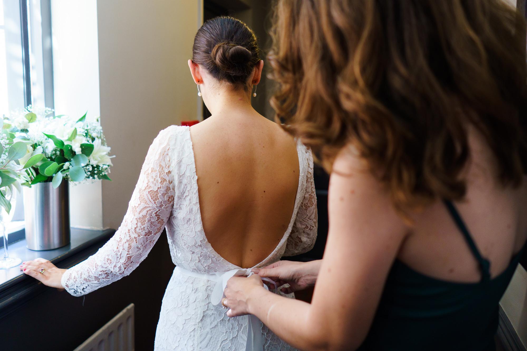 brdiesmaid helping zip bride's dress