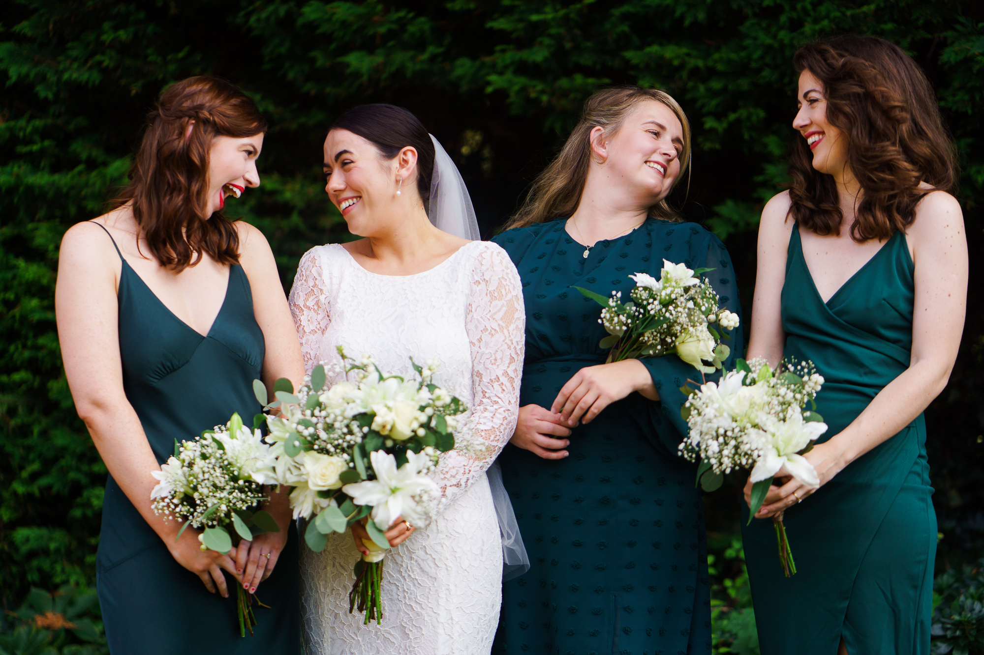 photo of bride and bridesmaids in green laughing